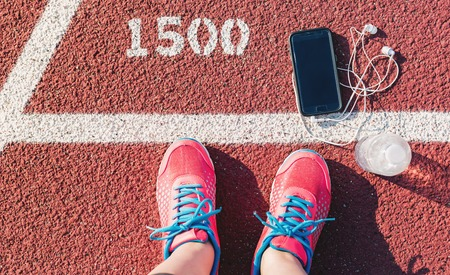 run down: Female runner looking down at her feet, phone and water bottle on a running track