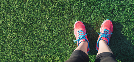 run down: Female runner looking down at her feet in a grass field Stock Photo