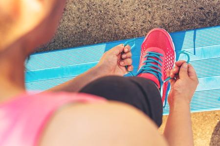 gradas estadio: Corredor femenino del cordón de sus zapatillas de deporte encendido en las gradas de un estadio Foto de archivo