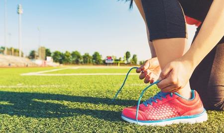 lacing sneakers: Female runner lacing her sneakers on a stadium field