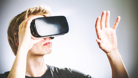 Blonde man met behulp van een virtual reality headset Stockfoto