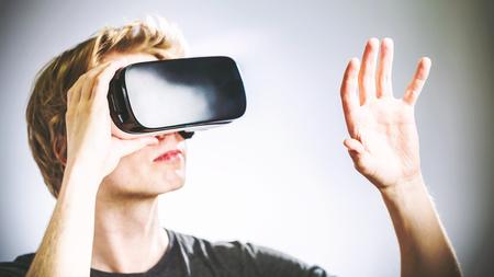 Hombre rubio usando un casco de realidad virtual Foto de archivo