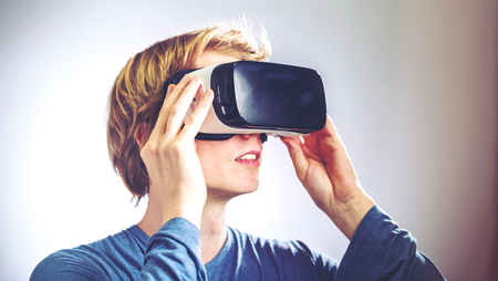ar: Blond man using a virtual reality headset Stock Photo
