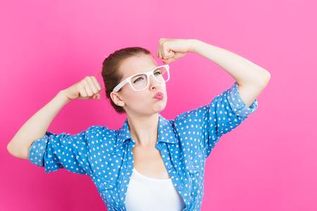 jovem mulher poderosa sobre um fundo rosa