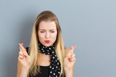 Jonge vrouw die haar vingers en wensen voor geluk
