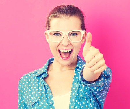 분홍색 배경에 엄지 손가락을 포기하는 행복 한 젊은 여자 스톡 콘텐츠
