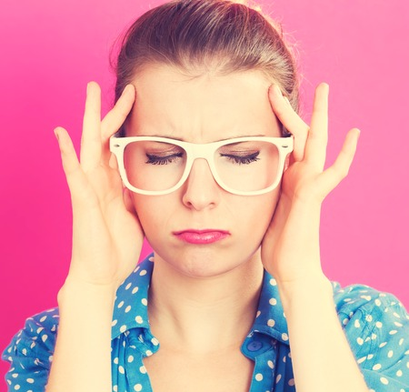 Young woman feeling stressed on a pink background