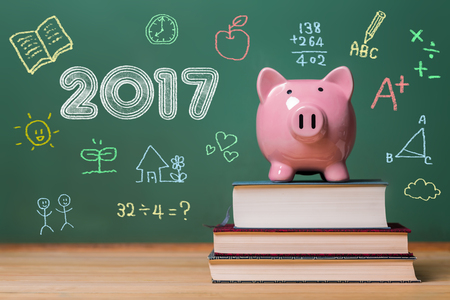 text books: Year 2017 text with pink piggy bank on top of books with chalkboard