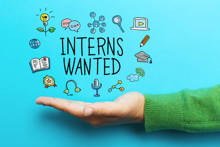 Interns Wanted concept with hand on blue background