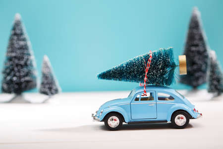 christmas toy: Car carrying a Christmas tree in a snow covered miniature evergreen forest Stock Photo