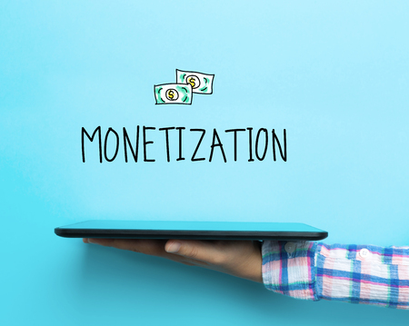 monetize: Monetization concept with a tablet on blue background