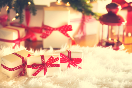 under tree: Christmas gift boxes on a white carpet at night