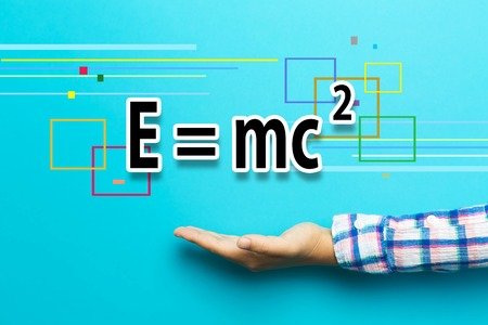 Mass-Energy Equivalence concept with hand on blue background