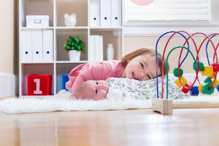 Glückliches Kleinkindmädchen mit ihrem neugeborenen Schwester spielen