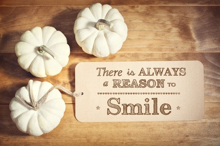 reason: There is Always a Reason to Smile message with small white pumpkins on wooden table