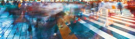 Movimento folla offuscata convergono allo Shibuya Crossing, una delle strisce pedonali più trafficati del mondo. Tokyo, Giappone