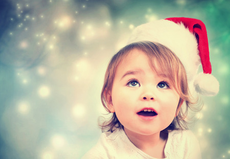smiling faces: Happy Toddler girl with a Santa hat