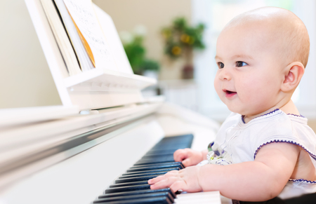 Baby girl playing the piano in her house 版權商用圖片