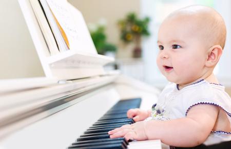 meisje van de baby het spelen van de piano in haar huis