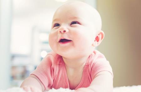Heureux bébé nouveau-né fille avec un grand sourire