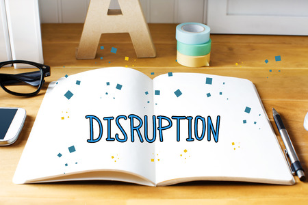 disruption: Disruption concept with notebook on wooden desk