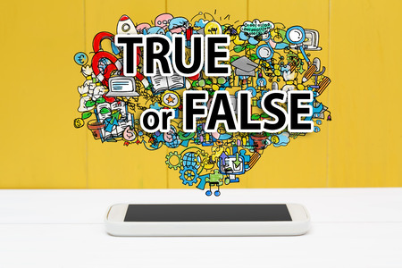 true or false: True or False concept with smartphone on yellow wooden background