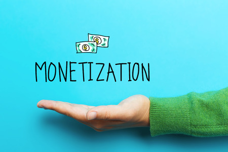 monetization: Monetization concept with hand on blue background