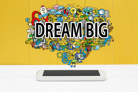 Dream Big concept with smartphone on yellow wooden background