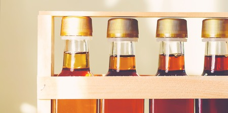 jarabe: Four grades of of maple syrup in glass bottles in sunlight
