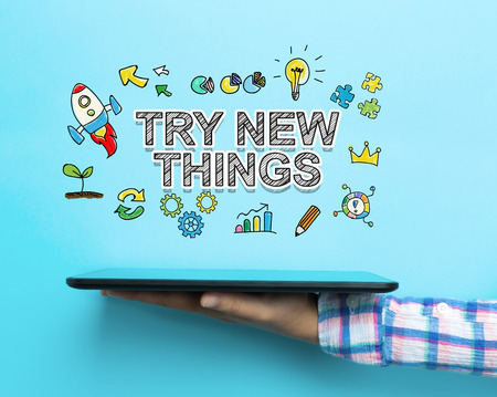 try: Try New Things concept with a tablet on blue background