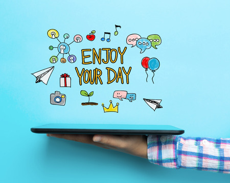 Enjoy Your Day concept with a tablet on blue background Stock Photo
