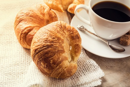 bread: Batch of croissants on a rustic wooden table with coffee