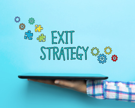 downsizing: Exit Strategy concept with a tablet on blue background Stock Photo
