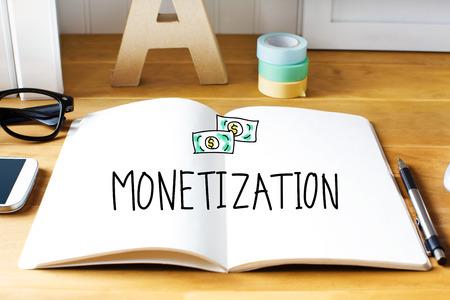 monetization: Monetization concept with notebook on wooden desk