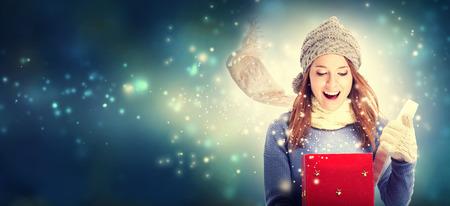 クリスマス プレゼント ボックスを開く幸せな若い女