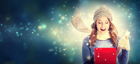 Felice giovane donna che apre un regalo di Natale casella Archivio Fotografico - 64891147