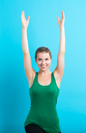 woman stretching: Happy young woman stretching on a blue background