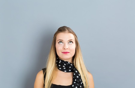 Young woman in a thoughtful pose on a gray background