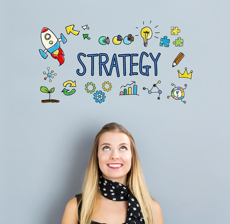 small business woman: Strategy concept with happy young woman on a gray background Stock Photo