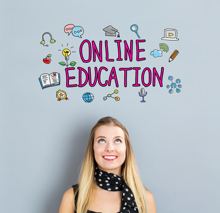 small business woman: Online Education concept with happy young woman on a gray background Stock Photo