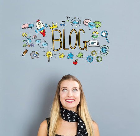 small business woman: Blog concept with happy young woman on a gray background Stock Photo
