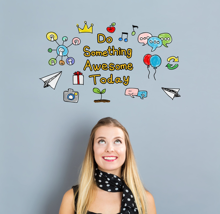 small business woman: Do Something Awesome Today concept with happy young woman on a gray background