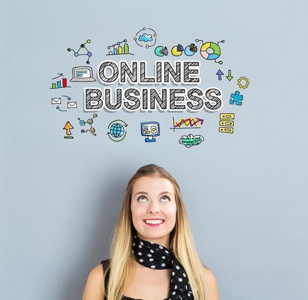 Concept d'affaires en ligne avec une jeune femme heureuse sur un fond gris Banque d'images