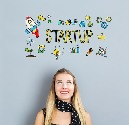 young businesswoman: Start Up concept with happy young woman on a gray background