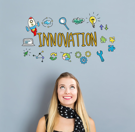 small business woman: Innovation concept with happy young woman on a gray background Stock Photo