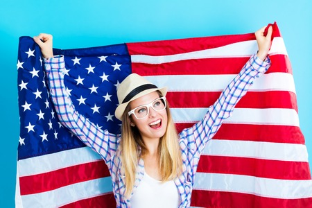 study: Happy young traveling woman holding American flag Stock Photo