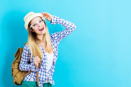 青色の背景に幸せな若い旅行女