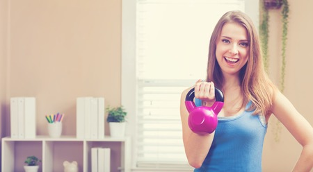 jovenes felices: Happy young woman working out with a kettlebell in her house Foto de archivo