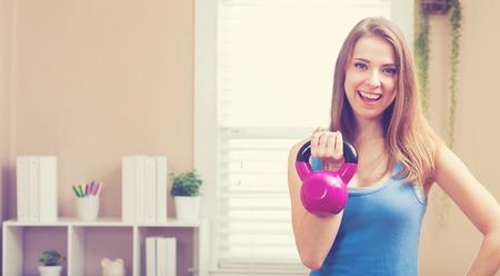 Mujer joven feliz que se resuelve con una pesa en su casa