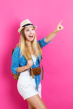 Mujer que viaja joven y feliz sobre un fondo de color rosa Foto de archivo - 63882383
